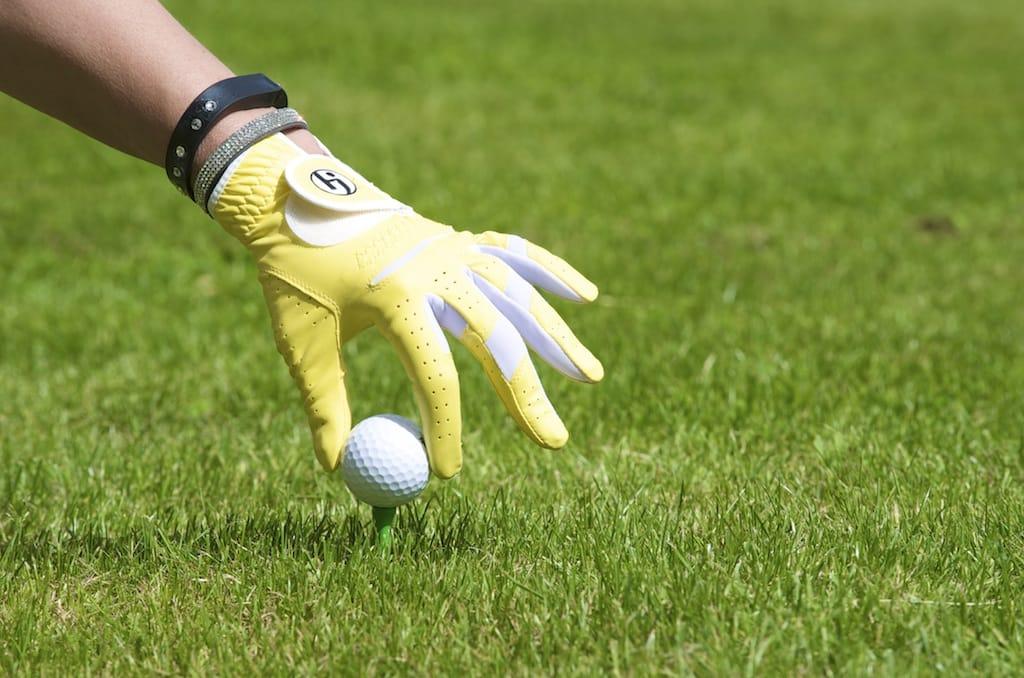 Hand placing golf ball on tee