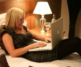 Woman working on laptop in hotel room