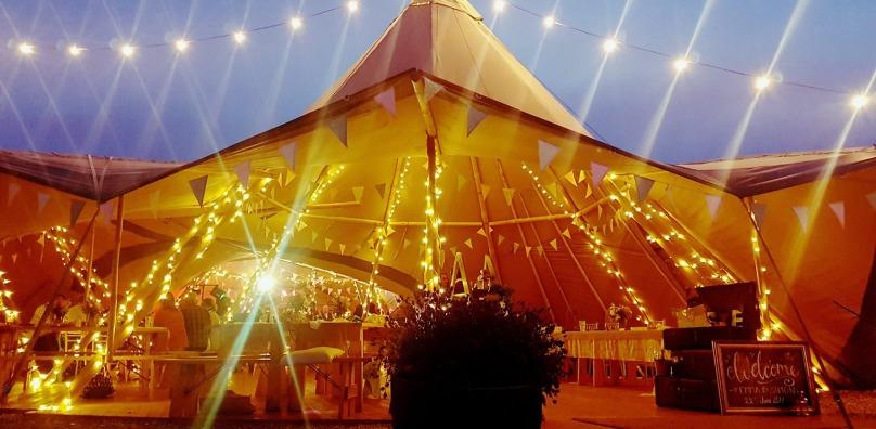 Lit tipi wedding at dusk
